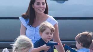 Prinz George spielt mit einer Pistole, während Herzogin Kate zusieht