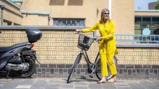 Königin Máxima der Niederlande strahlt in gelbem Outfit neben ihrem Fahrrad auf dem Weg zu einem Ausstellungsbesuch.