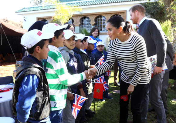 Prince Harry and Duchess Meghan greeting the children